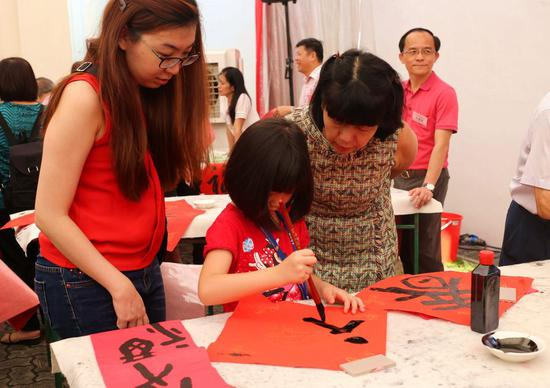 A girl participates in a Chinese Huichun calligraphy convention in Singapore, on Jan. 15, 2017. (Xinhua/Bao Xuelin)