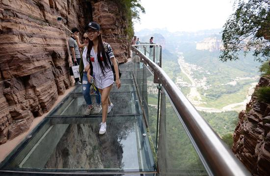 Tourists experience a glass walkway in a scenic area in Handan, Hebei Province, in September. (Photo / China Daily)