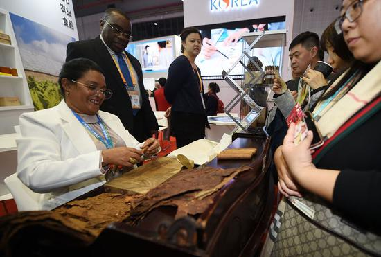 An exhibitor makes cigars at the booth of Cuba at the first China International Import Expo (CIIE) in Shanghai, east China, Nov. 6, 2018. (Xinhua/Han Yuqing)