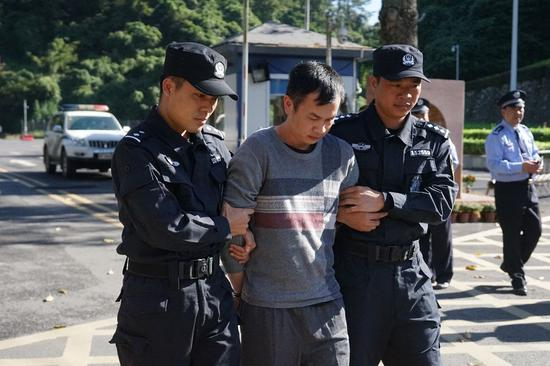 Hoang Minh Thong, a fugitive suspected of smuggling drugs, is escorted by police officers in south China's Guangxi Zhuang Autonomous Region, on Oct. 29, 2019. (Xinhua/Hu Jiali)