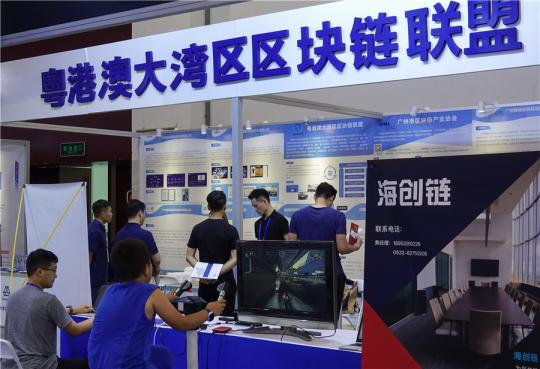 Employees of a Guangdong-based blockchain firm work at the company booth during a high-tech exhibition in Qingdao, Shandong Province. (Photo provided to China Daily)
