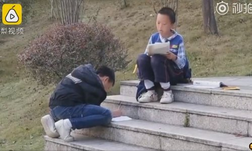 Annoyed by parents, two schoolboys finish homework at roadside