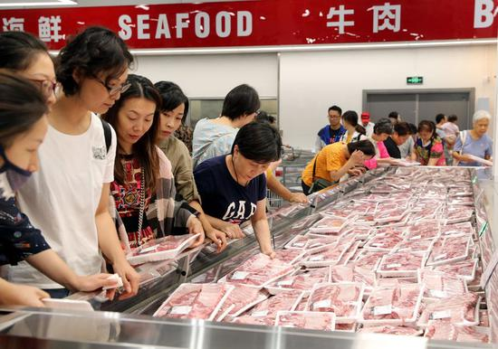Customers buy fresh pork in a Costco warehouse store in Minhang District, east China's Shanghai, Sept. 19, 2019. (Xinhua/Liu Ying)