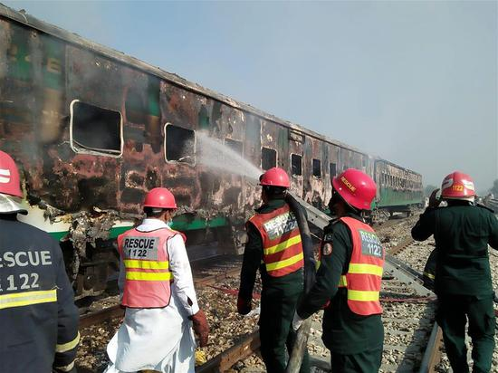 Photo taken with mobile phone shows rescuers working after a passenger train caught fire in Rahim Yar Khan district of Pakistan's east Punjab province on Oct. 31, 2019.  (Str/Xinhua)