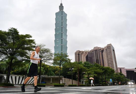 A citizen runs in front of the Taipei 101 skyscraper in Taipei, southeast China's Taiwan, on Oct. 1, 2019. (Xinhua/Chen Bin)