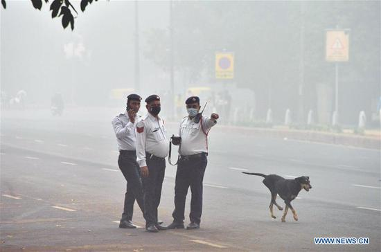 Traffic policemen with masks work in the street in smog near India Gate in New Delhi, India, on Nov. 3, 2019. (Photo by Partha Sarkar/Xinhua)
