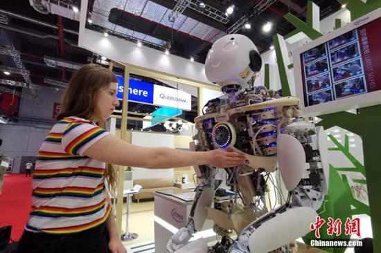 A visitor interacts with a robot on display at the second China International Import Expo in Shanghai, Nov. 4, 2019. (Photo: China News Service/Han Haidan)