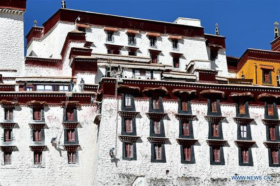 Workers paint wall of Potala Palace in Lhasa, Tibet