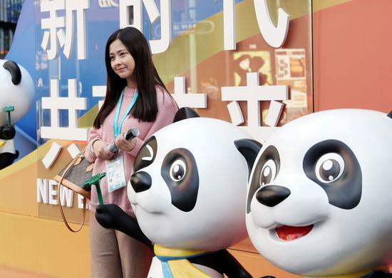 A visitor poses for photos with Jinbao, mascot of the China International Import Expo (CIIE), during the second CIIE in Shanghai, east China, Nov. 8, 2019. (Xinhua/Liu Ying)