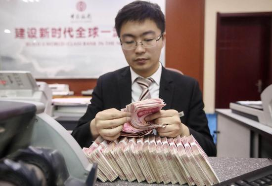 A cashier counts currency at a bank outlet in Taiyuan, capital of Shanxi Province. (ZHANG YUN/CHINA NEWS SERVICE)