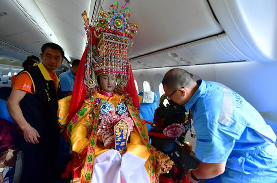 The cabin crew adjust the seat for the statue of Mazu on the airplane departing from Xiamen, Nov. 14, 2019. (Xinhua/Wei Peiquan)