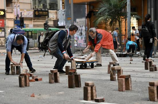 Hong Kong residents come out to clear roadblocks built by rioters