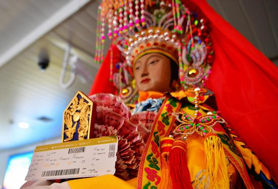 The goddess statue and her boarding pass (Xinhua/Wei Peiquan)
