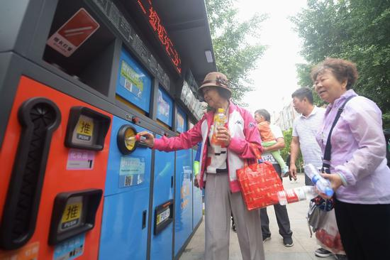 Residents throw plastic bottles in a trash bin with detailed sorting instructions in Beijing. (WEI TONG/FOR CHINA DAILY)
