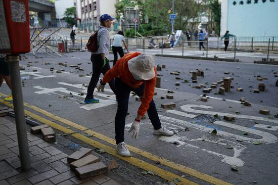 Hong Kong residents clear barricades, mourn innocent victim