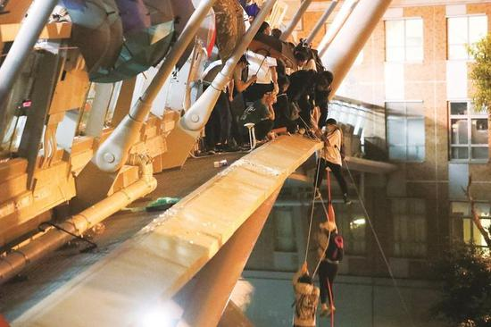 Radical protesters at Hong Kong Polytechnic University try to escape police siege by rappelling down ropes suspended from a footbridge in Hong Hum. (PHOTO / CHINA DAILY)
