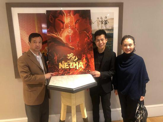 Yi Qiao (2nd R), CEO of animation shingle Coloroom Pictures, poses with a poster of