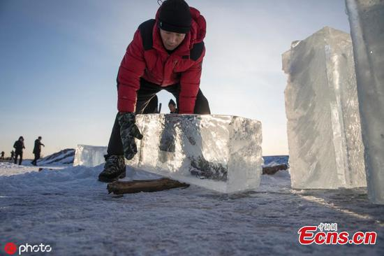 Workers collect ice from river in Mohe, NE China's Heilongjiang