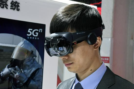 A staff member displays a Mixed Reality (MR) terminal device at the 2019 World 5G Convention in Beijing, capital of China, Nov. 21, 2019. (Xinhua/Ren Chao)
