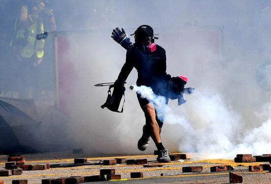 A rioter throws tear gas outside the Hong Kong Polytechnic University in south China's Hong Kong, Nov. 17, 2019. (Xinhua)