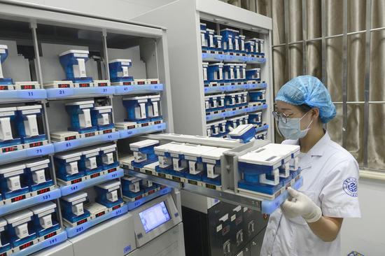 A pharmacist puts drugs into a machine at a smart dispensary in Zhuji City, east China's Zhejiang Province, Aug. 8, 2018. (Xinhua/Han Chuanhao)