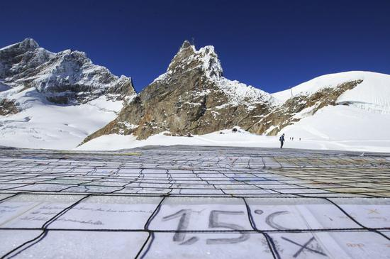 A gigantic postcard with the writing of 1.5 degrees Celsius is seen on the Aletsch glacier under Jungfraujoch in Switzerland, on Nov. 16, 2018. At the center of the postcard was a huge slogan reading