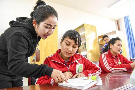 A teacher (1st L) instructs a trainee at a reading room of the vocational education and training center in Hotan county of Hotan Prefecture, northwest China's Xinjiang Uygur Autonomous Region, Oct. 7, 2018. (Xinhua/Hu Huhu)