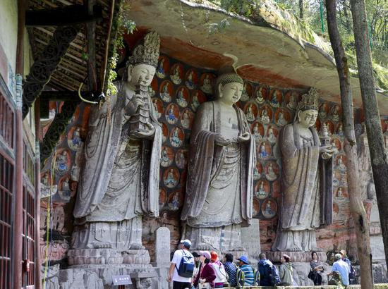 Tourists view rock carvings at the Dazu Rock Carvings scenic area in Dazu District of Chongqing, southwest China, March 29, 2019. The carvings dating back to the 9th to 13th centuries were placed on the world heritage list by the UNESCO in 1999. (Xinhua/Liu Chan)
