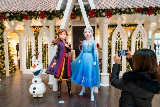 A visitor takes a snapshot at a Frozen 2-themed exhibition in a shop in downtown Shanghai. (Photo: Wang Gang/ For China Daily)