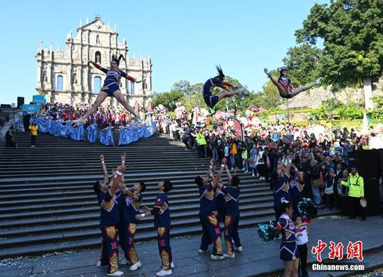 Performers take part in the Macao International Parade in Macao, south China, Dec. 8, 2019. The parade was held to celebrate the 20th anniversary of Macao's return to the motherland.  (Photo/China News Service)