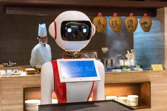 Photo taken on Oct. 19, 2019 shows a 5G-powered delivery robot in service, by which diners can order via the tablet, at a restaurant of Tong'an Hotel in Wuzhen, east China's Zhejiang Province. (Xinhua/Zhang Xiaoyu)