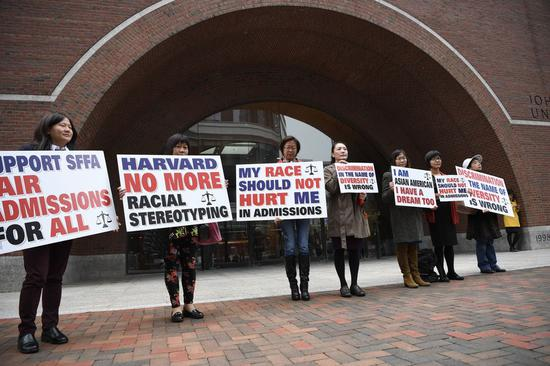 Demonstrators hold slogans in front of John Joseph Moakley United States Courthouse in Boston, Massachusetts, the United States, on Oct. 15, 2018. (Xinhua/Liu Jie)