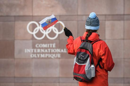 A supporter waves a Russian flag in front of the logo of the International Olympic Committee at its headquarters on Dec. 5, 2017 in Pully near Lausanne. (Xinhua/AFP)