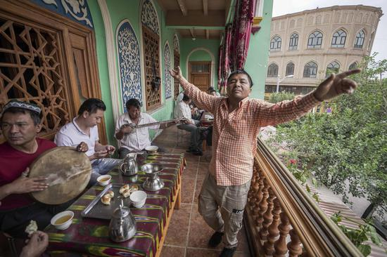 A local resident dances to the music at a tea house in the ancient city of Kashgar, northwest China's Xinjiang Uygur Autonomous Region, July 7, 2019. (Xinhua/Zhao Ge)