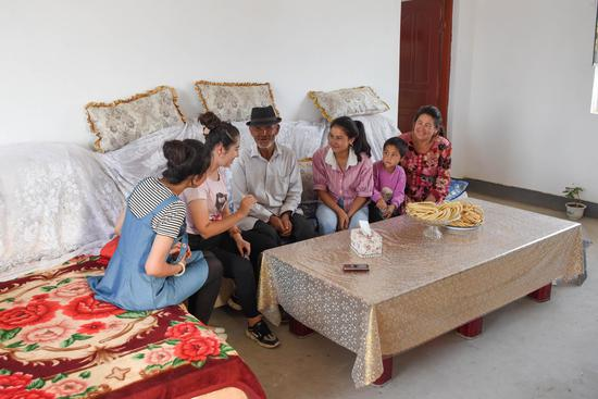 Residents chat at their new house in Yecheng County of Kashgar in northwest China's Xinjiang Uygur Autonomous Region, Aug. 19, 2019. (Xinhua/Ding Lei)