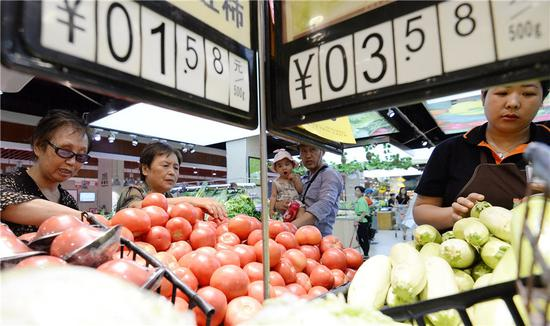Consumers buy vegetables at a supermarket in Handan, Hebei province. (Photo by Hao Qunying/For China Daily)