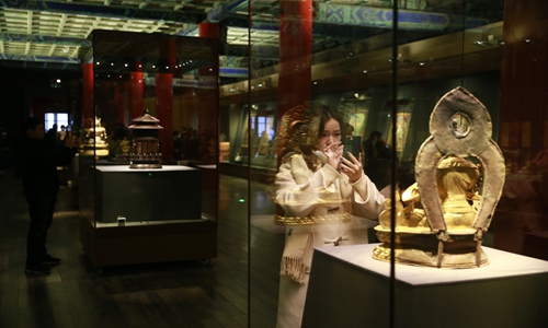 """A visitor takes picture of relics at an exhibition, titled """"the Fortune and Longevity of Sumeru: an Encounter between the Tashi Lhunpo Monastery and the Palace Museum,"""" which opened to public on Tuesday. (Photo: Li Hao/GT)"""