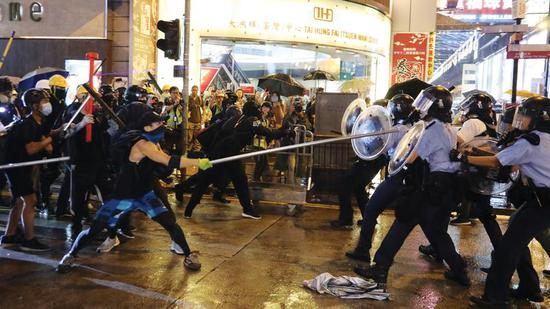 Radical protesters attack police officers with metal rods at an unauthorized assembly in Hong Kong. (Photo/China Daily)