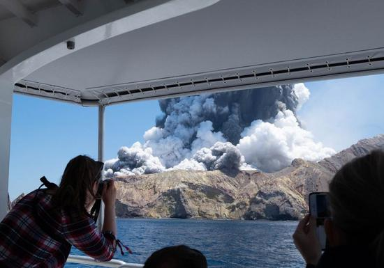 A person takes photos of volcanic eruption at New Zealand's White Island, Dec. 9, 2019. (Photo provided by Michael Schade/Handout via Xinhua)