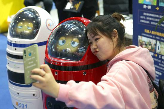 A visitor poses for photographs with smart education robots during a high-tech exhibition in Beijing. (Zou Hong/China Daily)