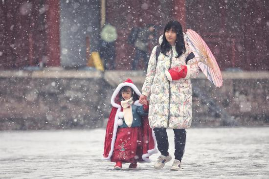 A woman and girl enjoy wintry scenery at Beijing's Working People's Cultural Palace as snow falls in the capital on Monday. (LIU CHANG/FOR CHINA DAILY)