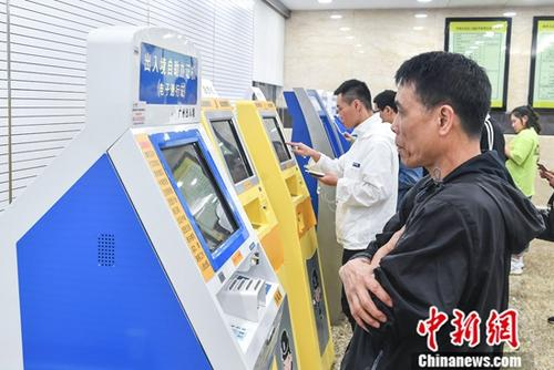 People check their information on a machine in Exit-Entry Administration Division of Guangzhou Public Security Bureau. (File photo/China News Service)
