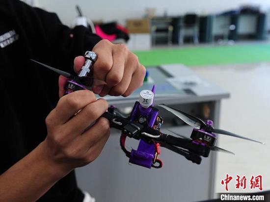 王铁林对无人机零件进行研究。 (照片/中国新闻社)