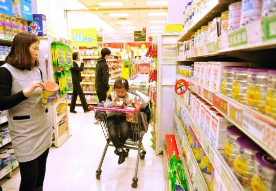 Consumers check out infant and toddler formulas at a supermarket in Qingdao, Shandong province. (Photo/China Daily)