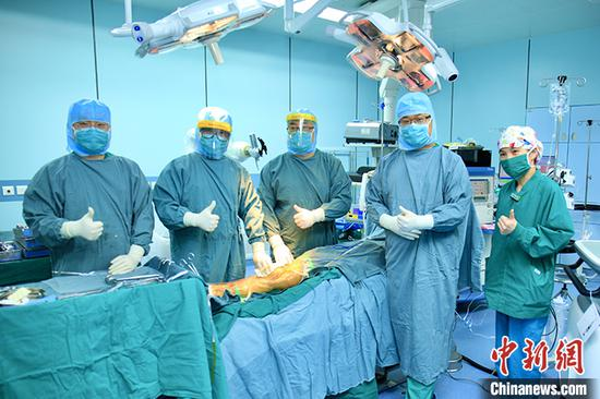 Doctors pose for a photo after China's first robotic Total Knee Arthroplasty (TKA) operation is successfully done in Beijing. (Photo/China News Service)