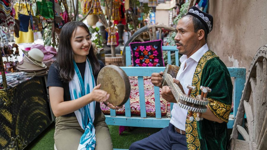 Local residents play music for tourists in the old town of Kashgar, northwest China's Xinjiang Uygur Autonomous Region, July 9, 2019. /Xinhua Photo