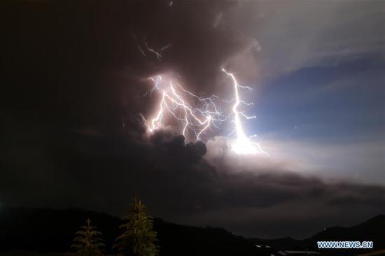"""2020年1月12日,菲律宾塔雅岱(Taaytay)爆发塔拉火山时,闪电闪烁。菲律宾将星期日塔拉火山喷发的预警等级提高至4级,等级为5级,并说:""""危险爆炸可能在数小时内爆发火山活动增加。 (新华社/鲁埃尔·乌马利)"""