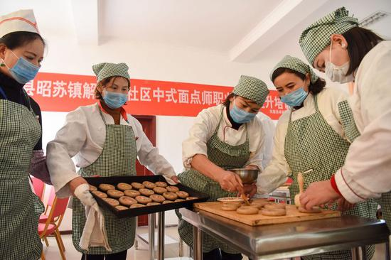 People practice making pasta during a vocational training class in Zhaosu County, northwest China's Xinjiang Uygur Autonomous Region, Dec. 14, 2019. (Xinhua/Ding Lei)