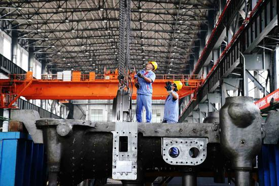 Employees work on the production line of a steam turbine manufacturer in Harbin, capital of Heilongjiang Province. (Photo/Xinhua)