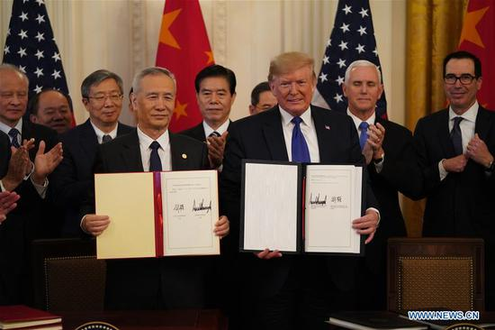 U.S. President Donald Trump and Chinese Vice Premier Liu He, who is also a member of the Political Bureau of the Communist Party of China Central Committee and chief of the Chinese side of the China-U.S. comprehensive economic dialogue, show the signed China-U.S. phase-one economic and trade agreement during a ceremony at the East Room of the White House in Washington D.C., the United States, Jan. 15, 2020. (Xinhua/Wang Ying)